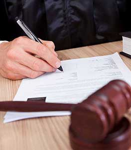 Image of a judge signing forms